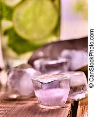 Chunks of ice cubes alcohol drink background on wooden...