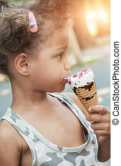 Cute little girl eating ice cream cone on the street