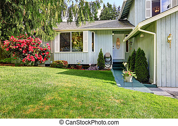 American blue house with white entrance door and green lawn in the front of the house.