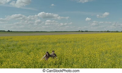 Happy couple go in rape field. Aerial View.