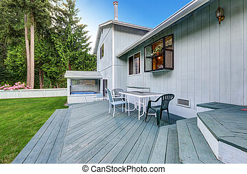 Blue walkout deck with patio table and chairs. View of hot tub.