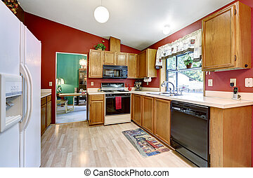Kitchen room with red wall, vaulted ceiling and dining table...