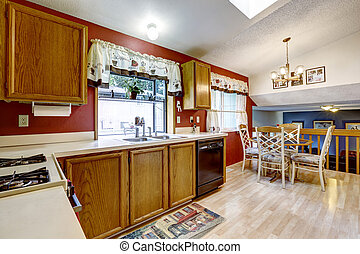 Kitchen room with red wall, hardwood floor and white fridge....