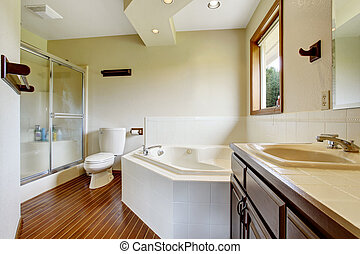 Master bathroom interior with glass shower, hardwood floor and white bathtub with tile trim