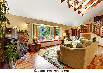 Light living room with hardwood floor and high ceiling with wooden beams.