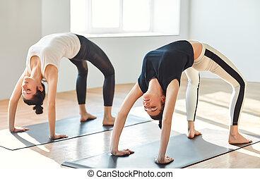 Two young women doing yoga asana upward bow (wheel) pose....