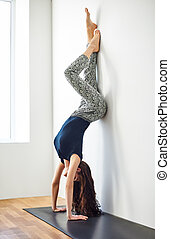 Beautiful sporty girl doing headstand yoga asana pose Adho...