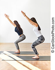 Two young women doing yoga asana chair pose. Utkatasana