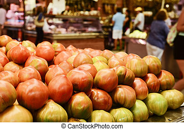 tomatoes on sale in a public market - closeup of some...