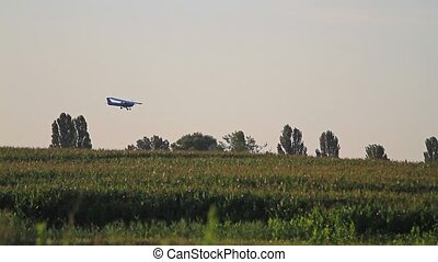 plane flying over corn field at sunrise,plane flies over a...