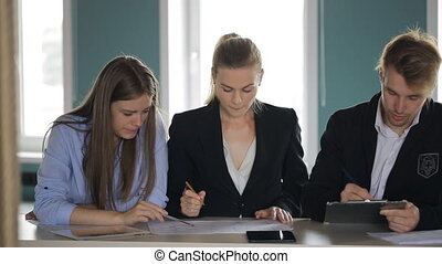 Women and a man sitting in a row at one table and conduct a business meeting.
