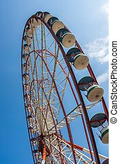 Underside view of a ferris wheel on sky background