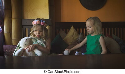 Two cute little girls are playing in a cafe