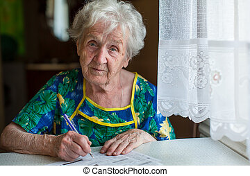 woman pensioner looks out the windo - Retired woman fills...