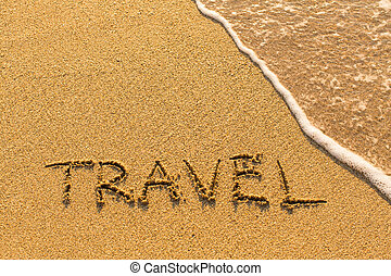 Travel - hand-written on the sand in line of the sea surf.