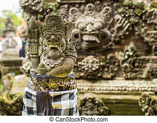 Traditional demon guards statue carved in stone on Bali