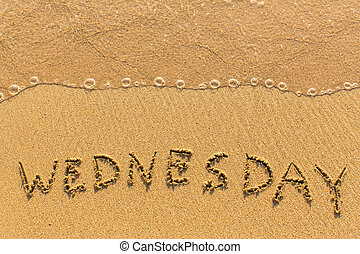 Wednesday - hand-written on the sand in line of the sea surf...