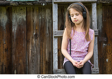 Little sad girl with headphones sitting on a wooden...