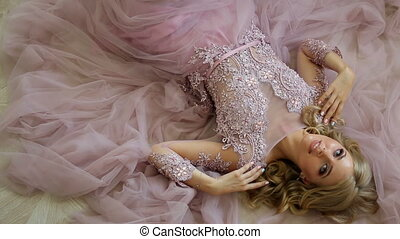 young sexy blonde girl in Lacy pink dress lying on the floor...