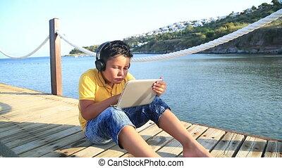 Boy playing digital tablet compute - Boy playing digital...