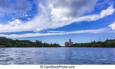 Riversides, speedboat and floating summer clouds 4K wide...