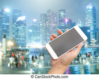 Hand holding smartphone with city people background