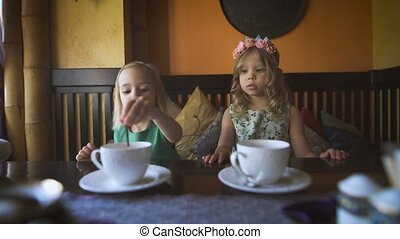 Two cute little girls are having tea in a cafe - Careless...
