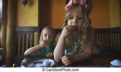 Two cute little girls are eating in a cafe