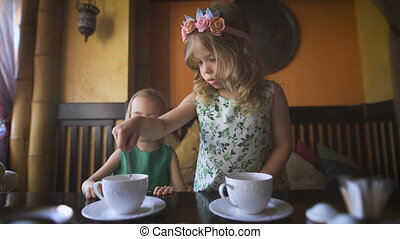 Two pretty little girls are having tea in a cafe