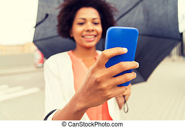 close up of woman with umbrella and smartphone - business,...