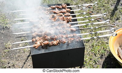Preparing tasty meat barbeque on skewers Shashlik grill over...