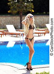 Beautiful sexy woman in black bikini on the sun-tanned slim...