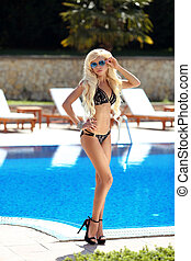 Beautiful fashion sexy woman in black bikini on the sun...