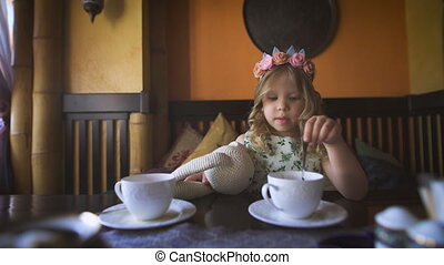 A little girl is having tea with her stuffed rabbit in a cozy cafe.