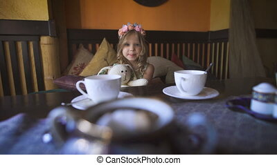A little happy girl is sitting on the couch at a cafe and...