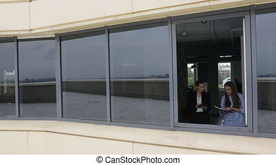 Two young women walked over to open window in office and talk.