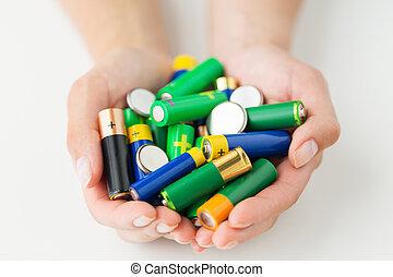 close up of hands holding alkaline batteries heap -...
