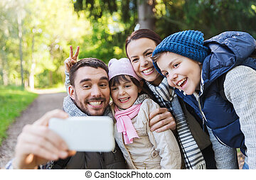 family with backpacks taking selfie by smartphone -...