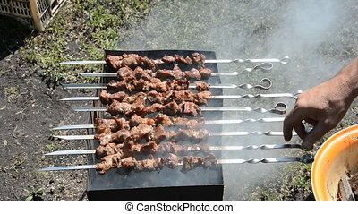 Meat rotating on a skewer. Close up of food grilling on...