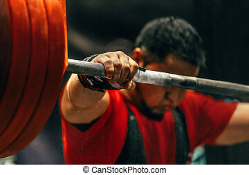 male powerlifter preparing for squats with a barbell during...