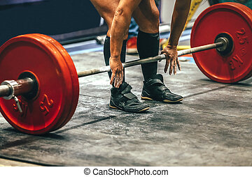 male powerlifter preparing for deadlift of barbell during...