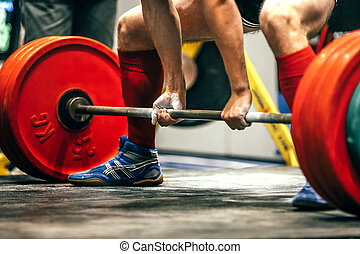 closeup of powerlifter to prepare exercise deadlift during...