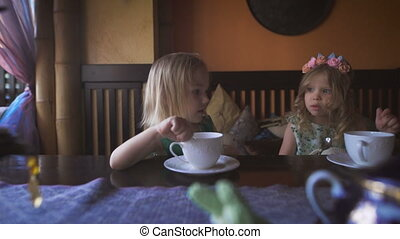 Two cute little girls are having tea in a cozy cafe -...