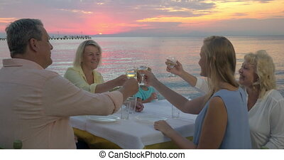 Family dinner by the sea at sunset - Big family in outdoor...