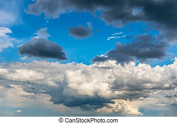 Blue sky background with white and dark clouds