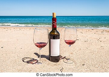 A bottle of wine and glasses on the beach - Romance near the...