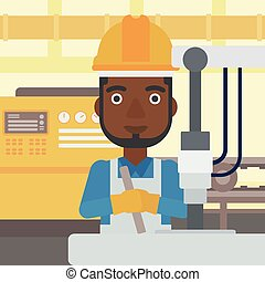 Man working on industrial drilling machine - An...