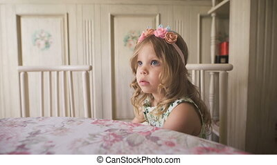Looking for inspiration. Thoughtful little girl looking away while sitting at the table in a bright room.