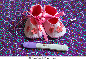Newborn baby girl booties and pregnancy test in bed