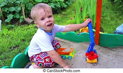 a child plays in the sandbox with the car Summer time